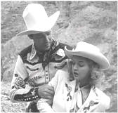 Dale Evans pretends to faint into the arms of Roy Rogers